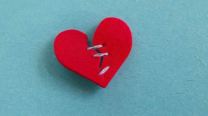 small red heart broken with threaded stitches