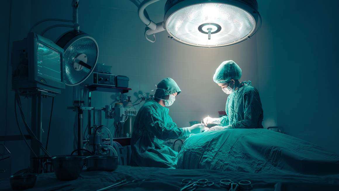 Surgeons team working with monitoring of patient in surgical operating room