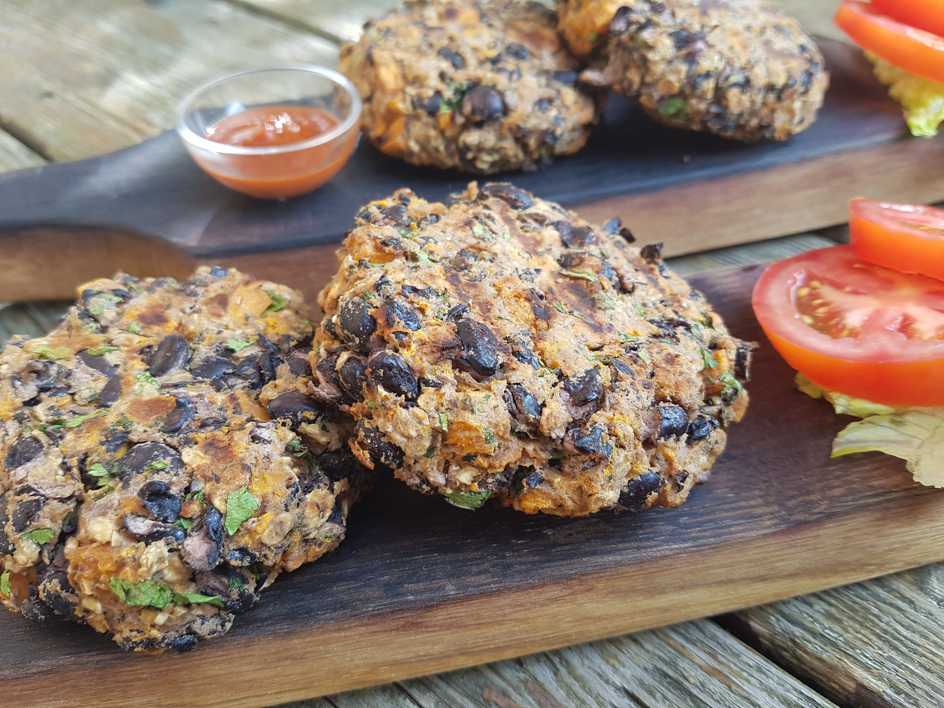 Sweet potato and black bean burger patties on wooden board with tomato slices