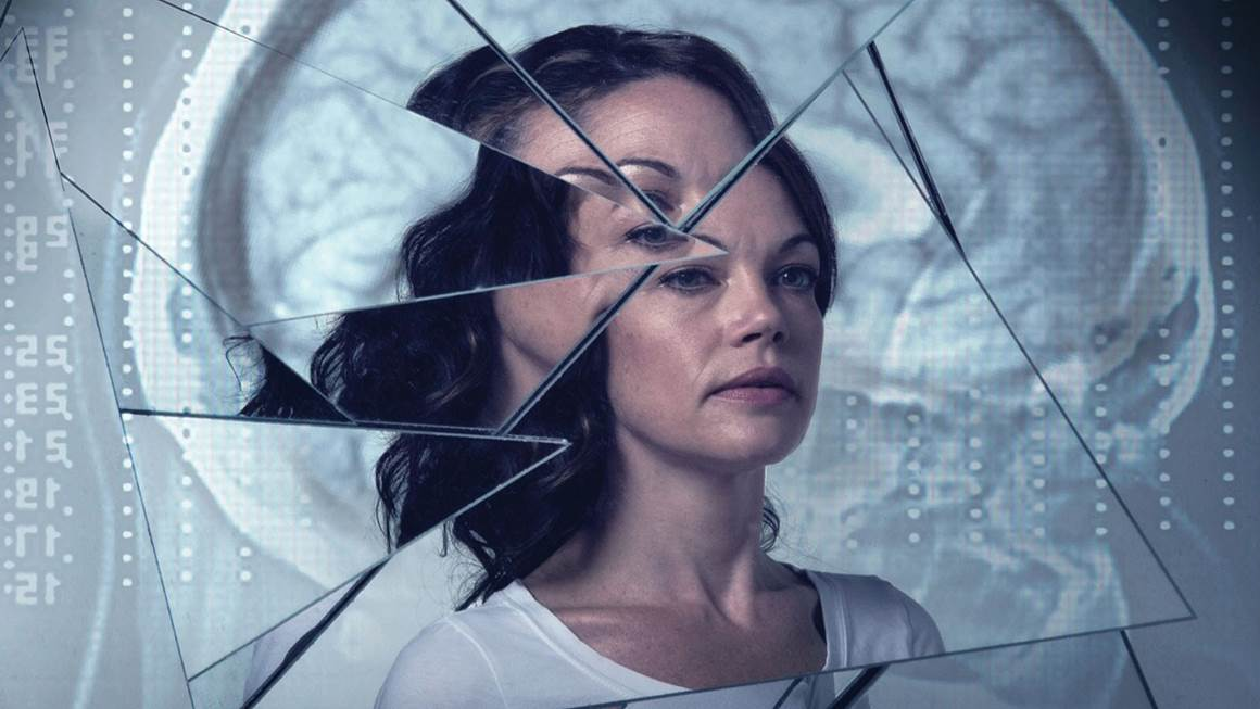 The face of a woman with long dark hair is reflected in a broken mirror