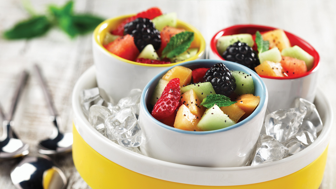 Three ramekins with diced melon, strawberries and berries