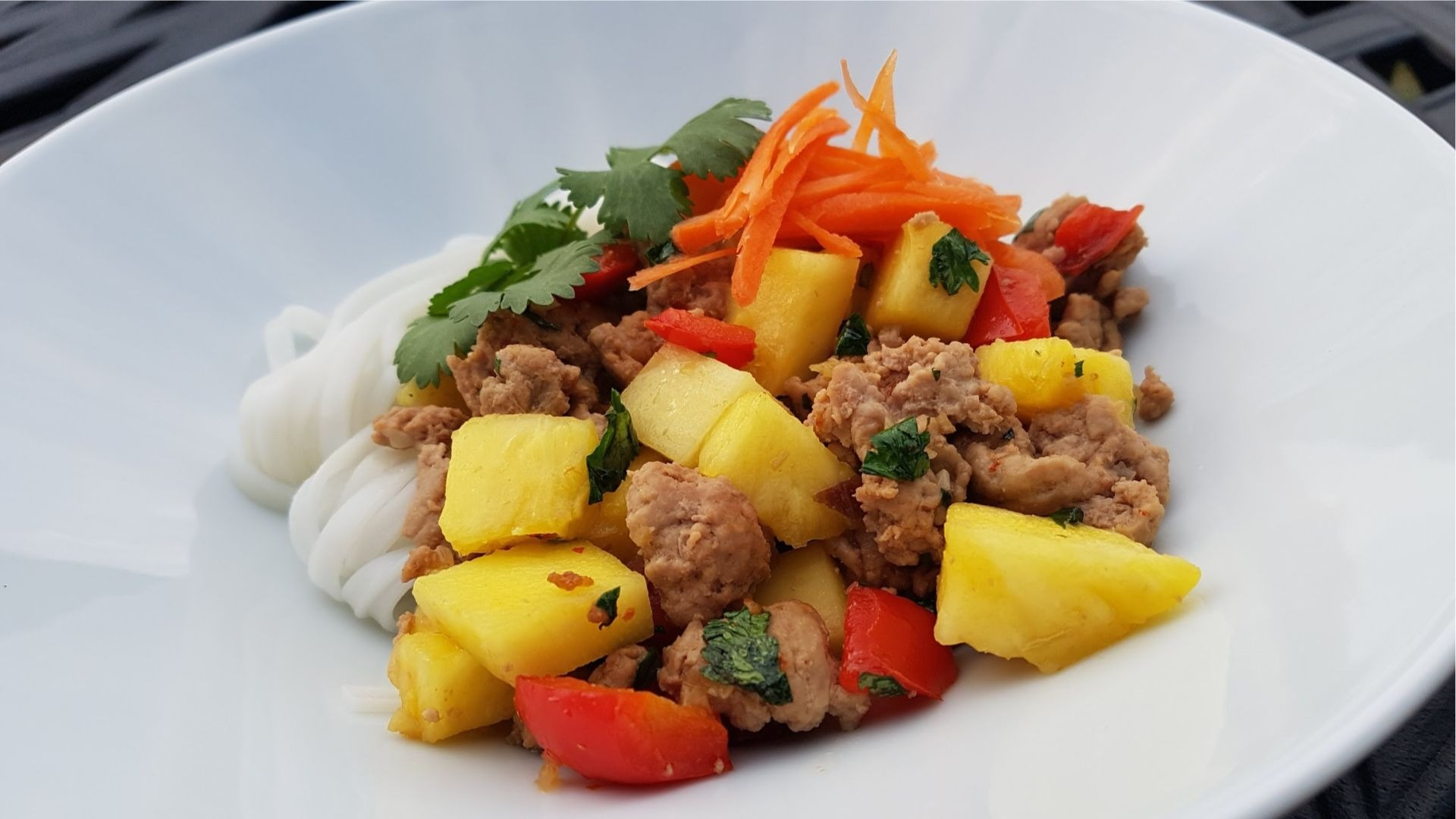 Bowl of noodles, minced turkey, pineapple, red peppers and grated carrots