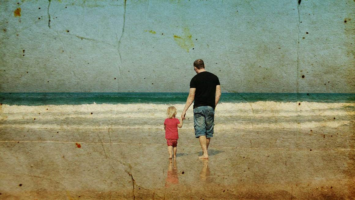 Vintage photo of daughter and father holding hands walking on beach