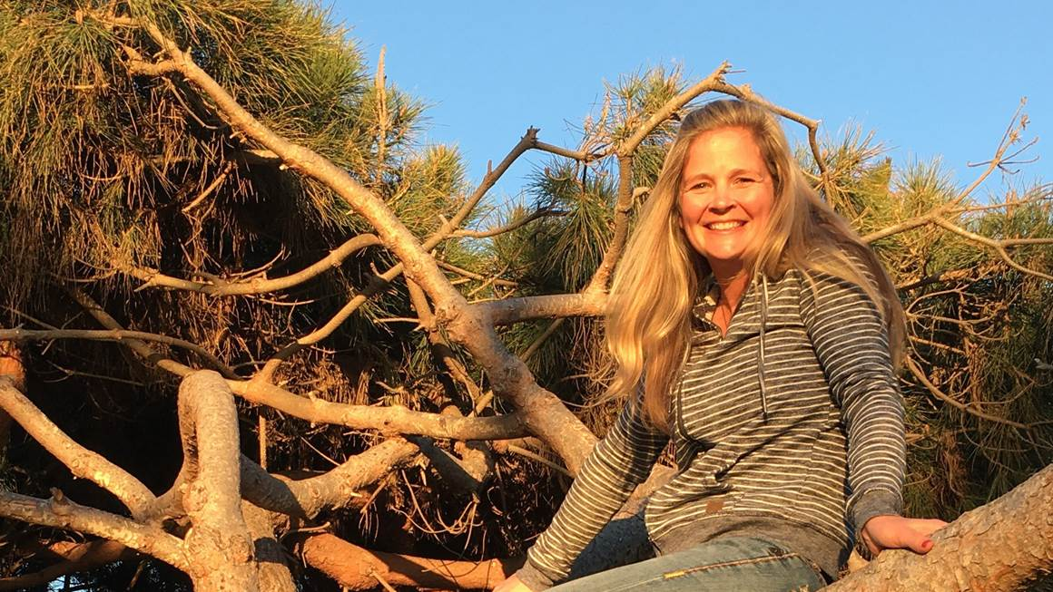Wendy Swain smiles at the camera while posed on a tree