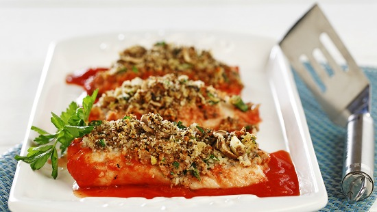 Cooked fish topped with herbs on white plate with red sauce