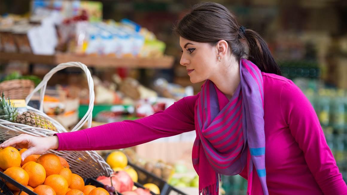 Woman buying oranges in supermarket