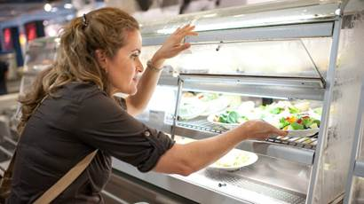 Woman choosing salad plate in cafeteria
