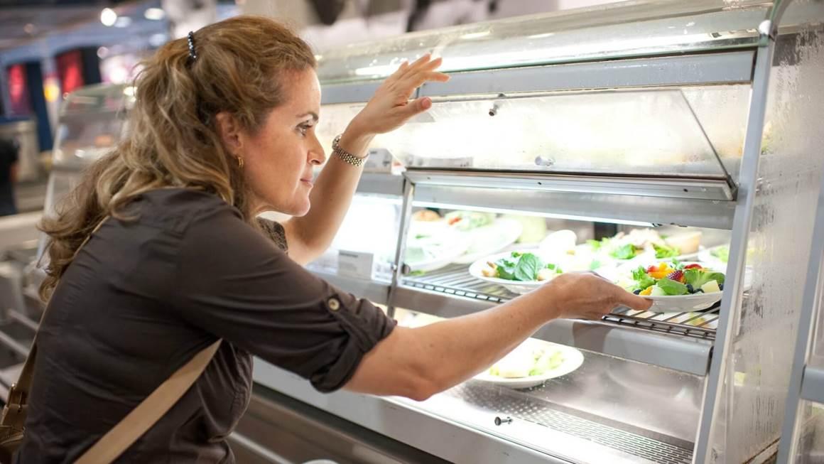Woman choosing salad plate in cafeteria