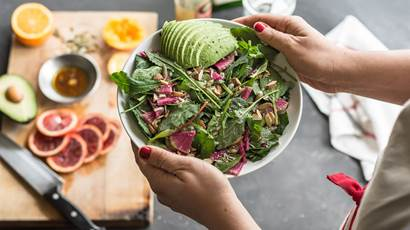 Woman holding fresh mixed green salad