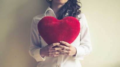 Woman holding red plush heart in front of her chest