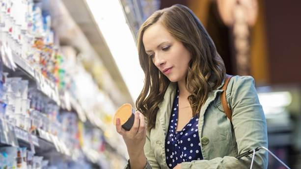 Woman in grocery store reading nutrition label on yogurt cup