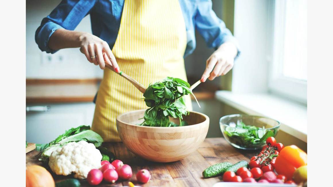A woman wearing a yellow apron tosses green salad in a wooden bowl.
