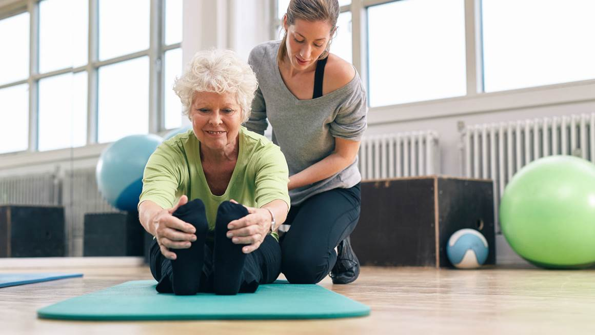 woman sitting on floor stretching legs with personal trainer