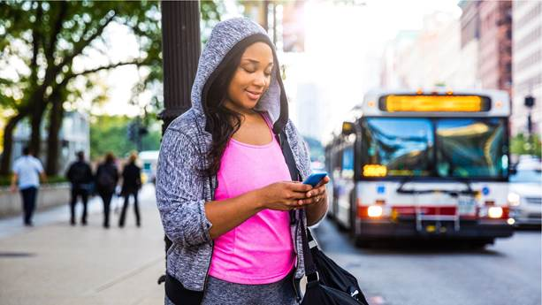 young woman waiting for bus checking her cell phone