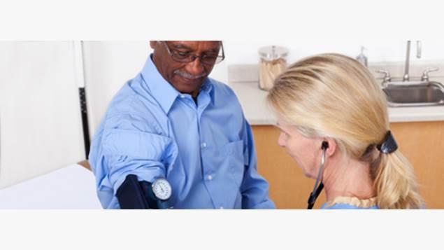 Man in blue shirt having his blood pressure taken