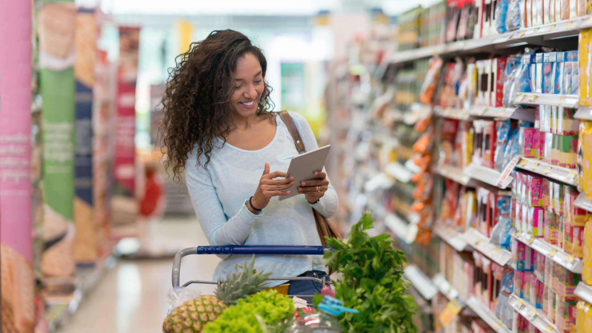 African american woman grocery shopping and looking at a shopping list on a digital tablet.
