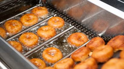 A dozen donuts frying in hot oil