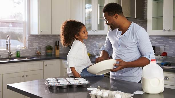 Father and daughter baking in kitchen