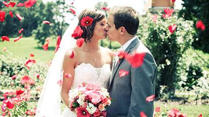 Bride and groom share a kiss with rose petal floating around them