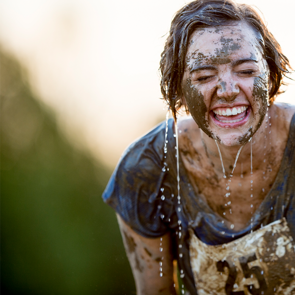 A smiling woman with mud on her face wears a race bib.