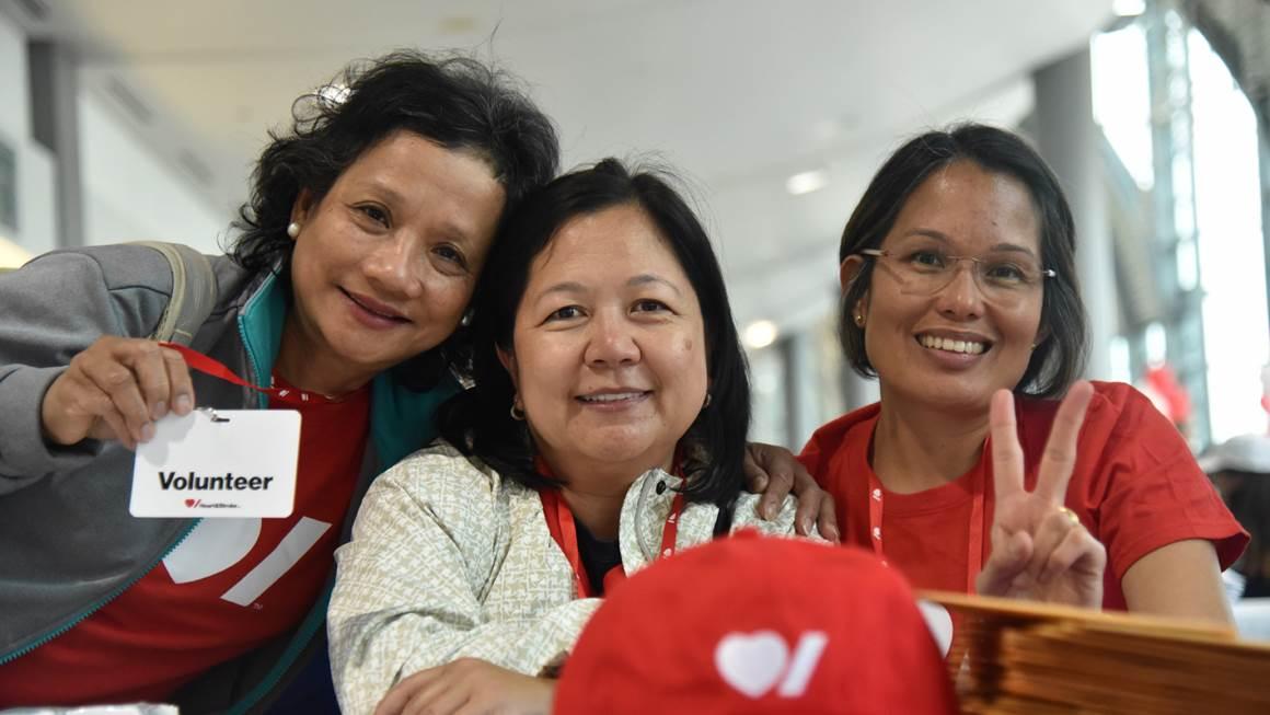 Three smiling volunteers wear Heart & Stroke gear.