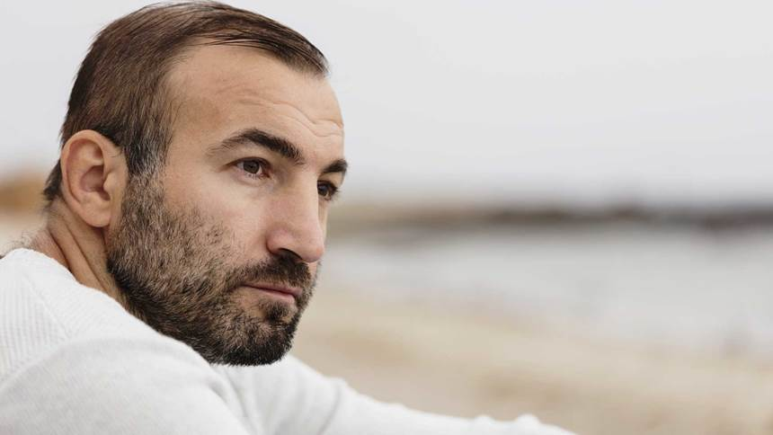 Male brunette with a beard in a white sweater looking at the sea