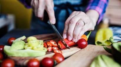 Woman cutting a chili pepper up close
