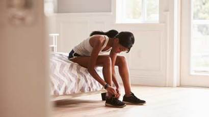Young woman in her bedroom tying her running shoe