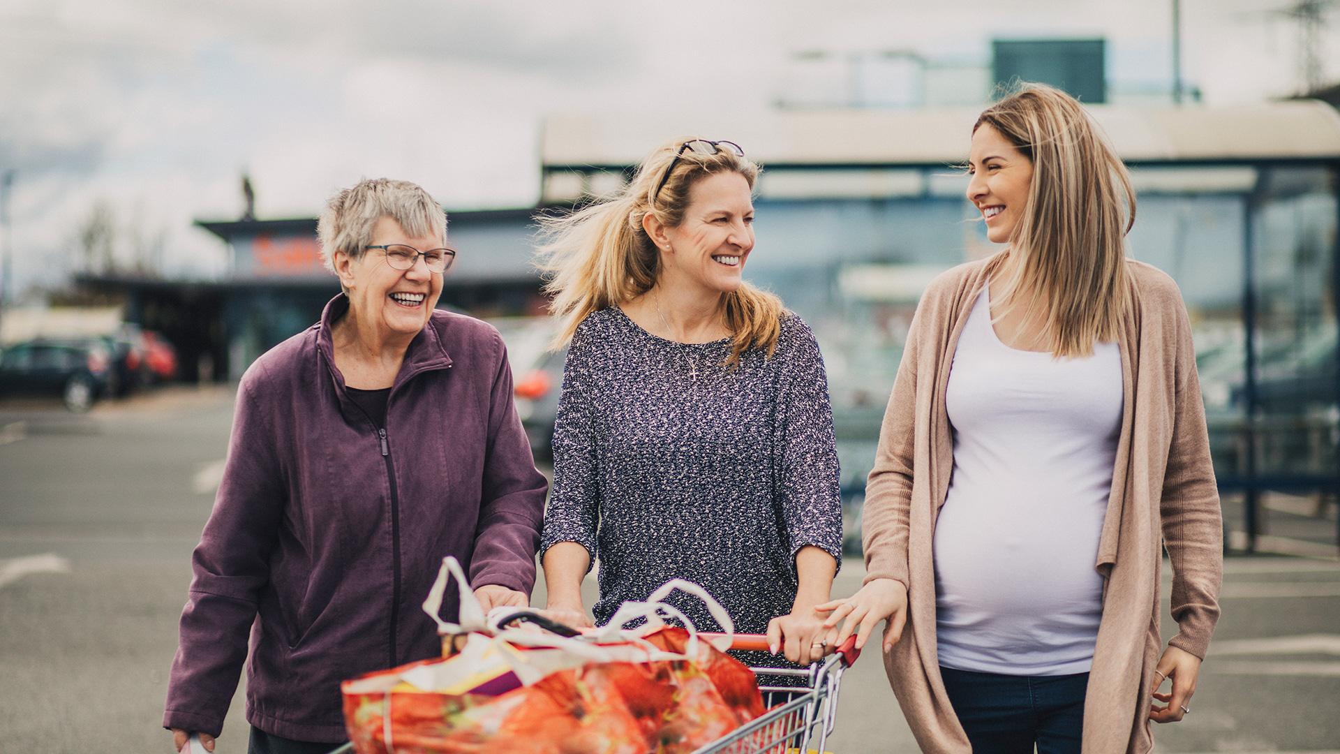 Older woman, middle aged woman and pregnant woman grocery shopping.