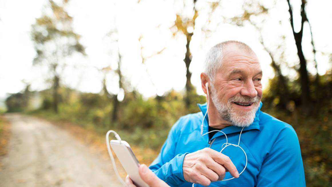 Man wearing blue shirt listening to music while going for a run.