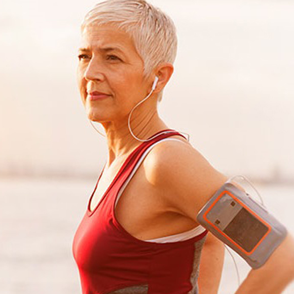 An older woman wears a red athletic top with a portable music player strapped to her arm.
