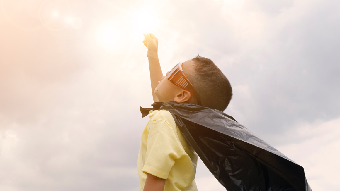 Boy wearing cape and sunglasses raising hand towards sun in the sky