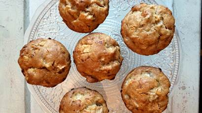 6 Apple maple cheddar muffins on a clear glass plate