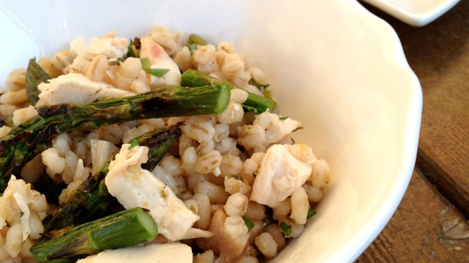 Barley asparagus chicken salad on a white plate and white bowl