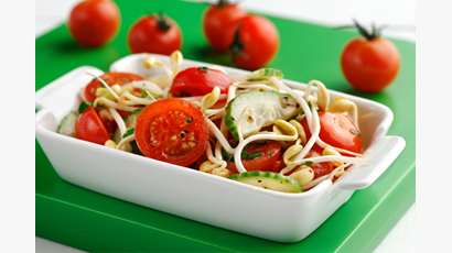 Bean sprouts and tomatoes in a white dish on a green board