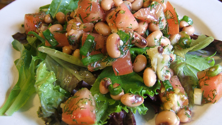 Black eyed pea and roasted garlic salad on a white plate