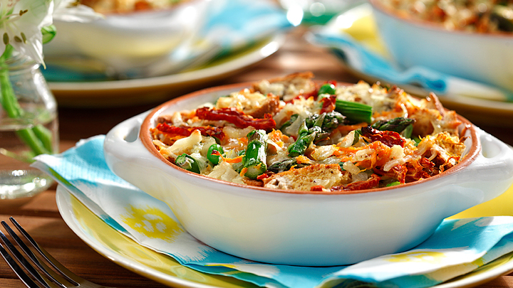 Breakfast strata primavera served in a white baking dish on top of a blue yellow and white napkin on
