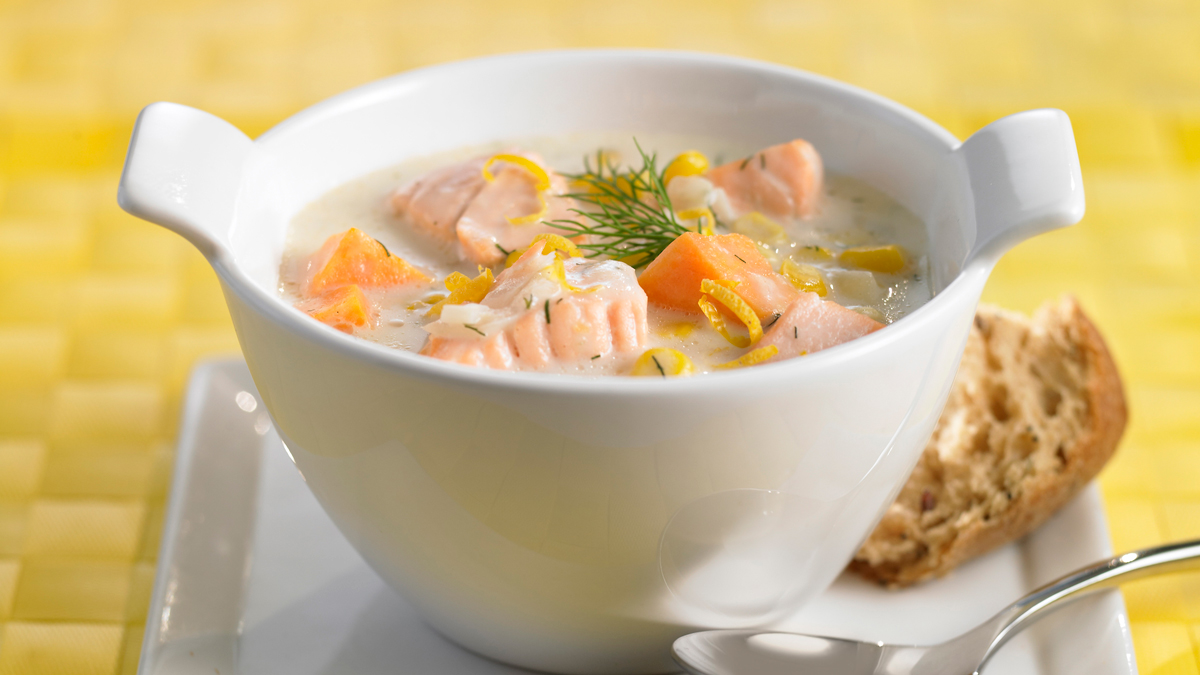 Corn sweet potato and salmon chowder in a white bowl