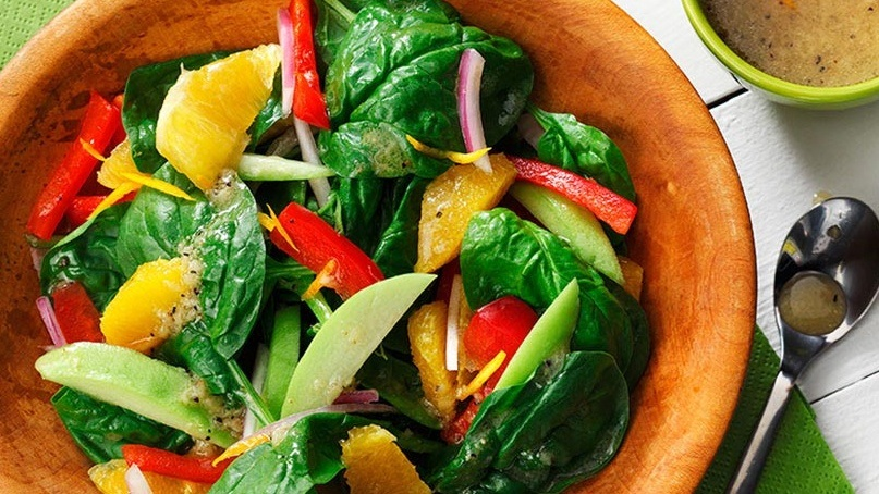 Bowl of spinach with orange segments, red peppers, onion in wooden bowl with vinaigrette in background