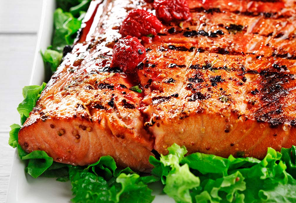 Grilled salmon with raspberry vinaigrette on bed of lettuce