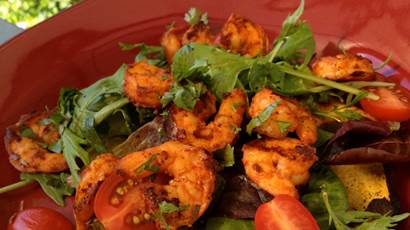 Grilled tortilla and shrimp salad in a red bowl