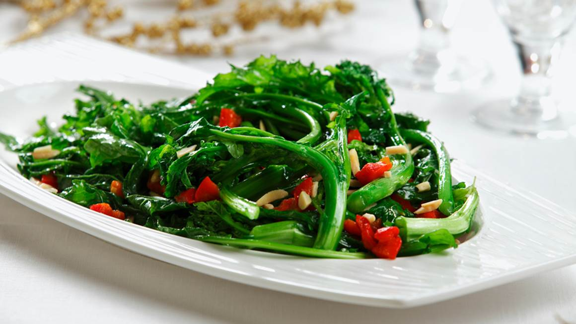 Holiday rapini saut served on a white plate on a white table cloth