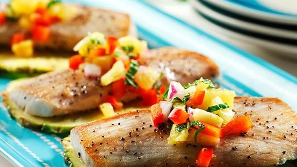 Three pieces of grilled mahi mahi with pineapple salsa on a blue plate