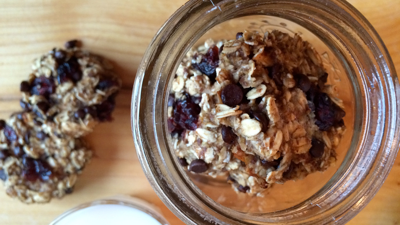 Oatmeal chococranberry cookies in a mason jar beside a cookie and glass of milk