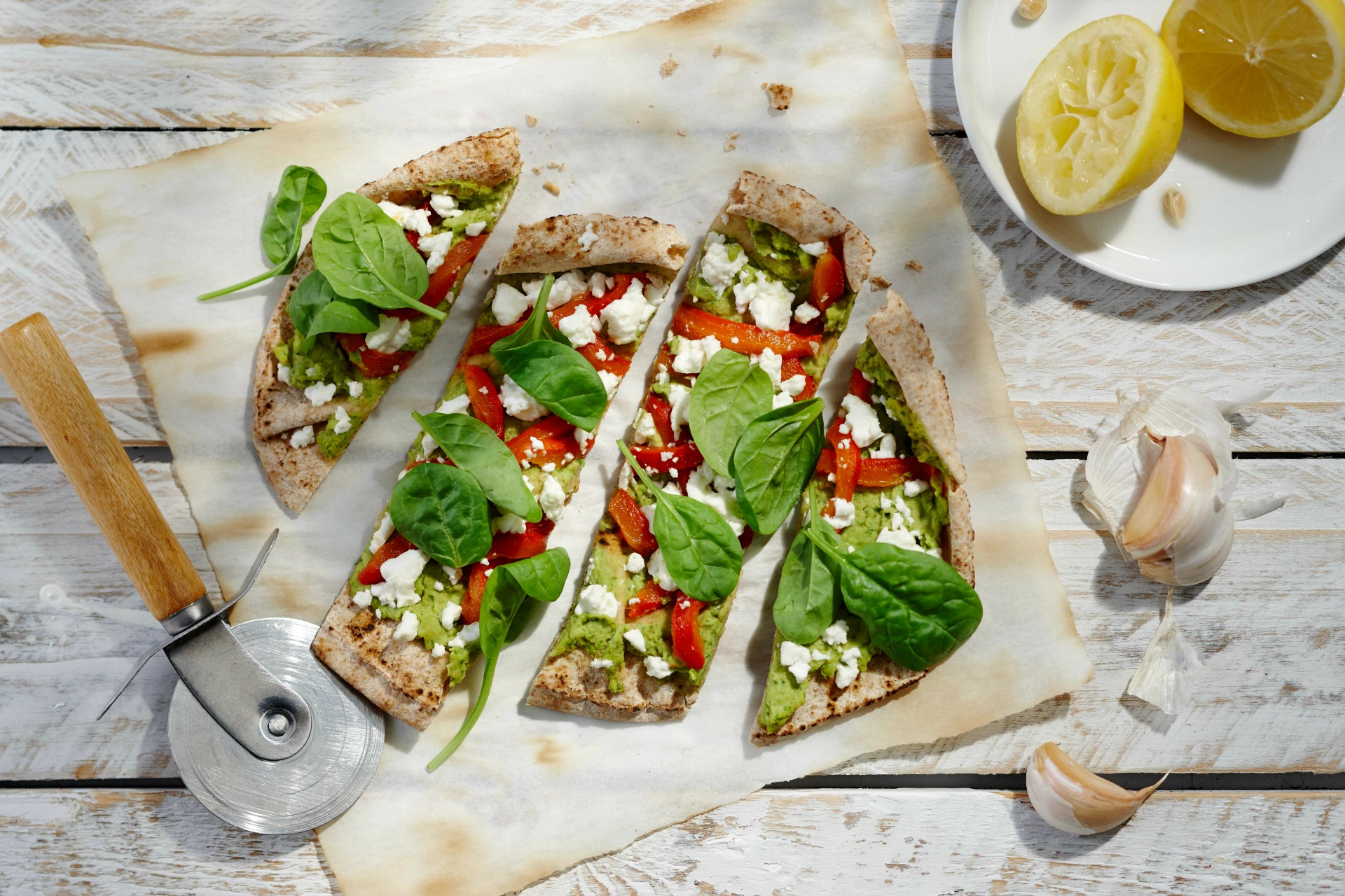 One roasted pepper, spinach and feta flatbread sliced on parchment paper, with a pizza cutter, garlic and lemon halved