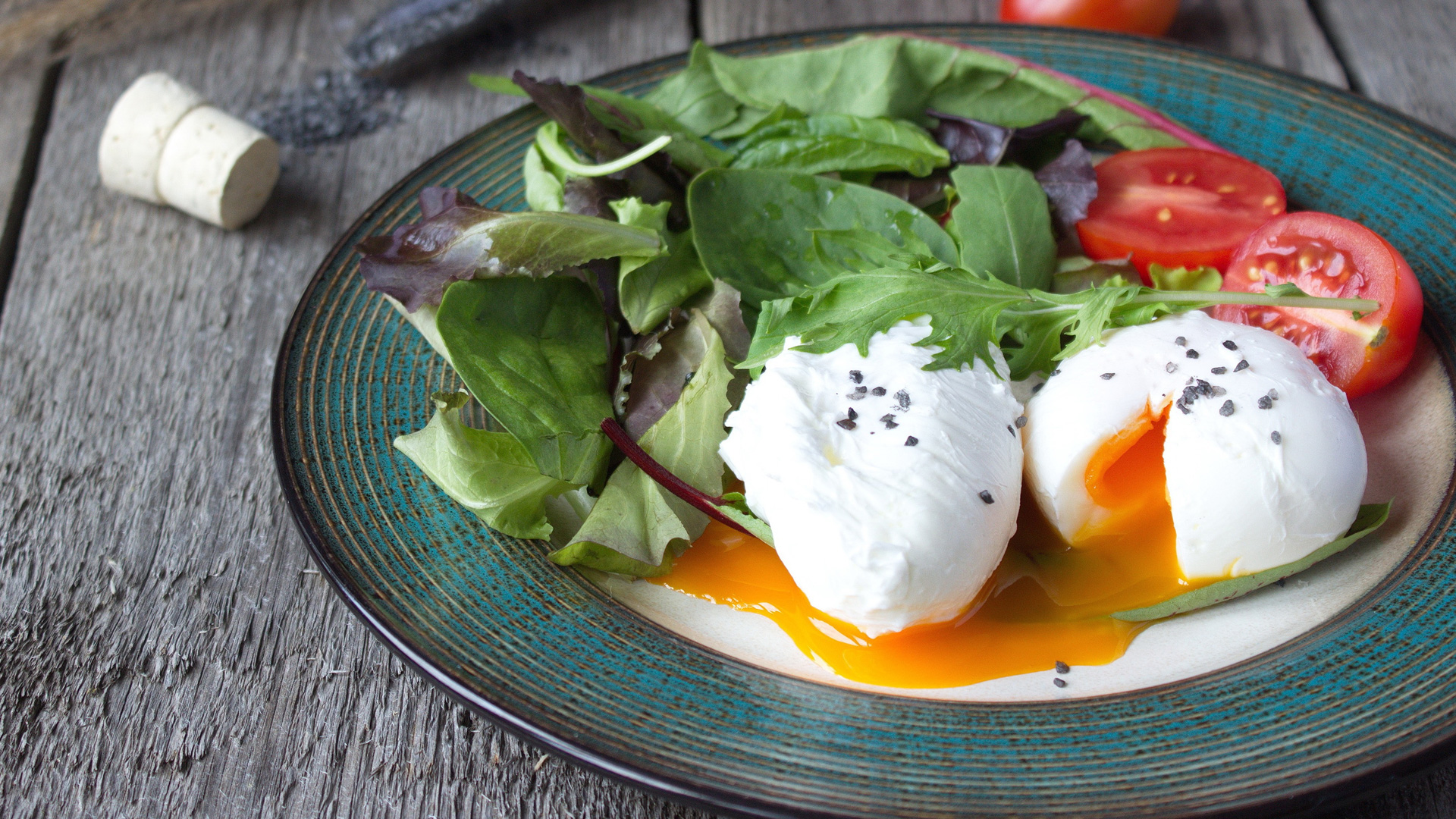 Poached eggs on plate with green salad and tomatoes