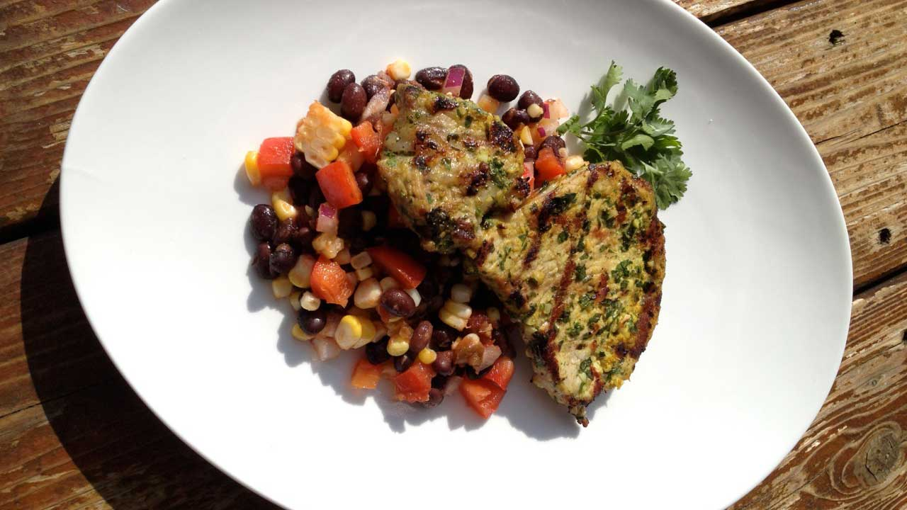 Pork with black bean salad on a large white plate on a wooden table