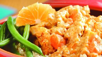Close up of cooked chicken, green beans, rice and orange segment