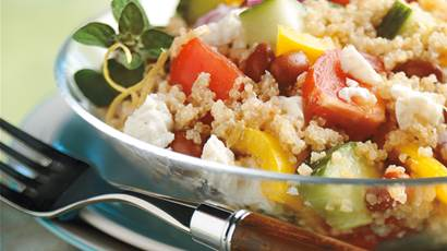 Quinoa Greek salad in a clear bowl with a fork