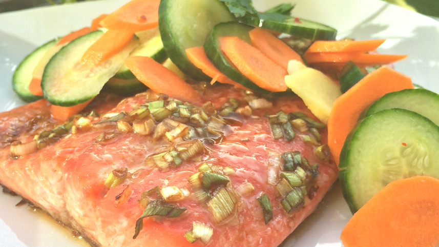 Rainbow trout with ginger carrot and cucumber on a white plate